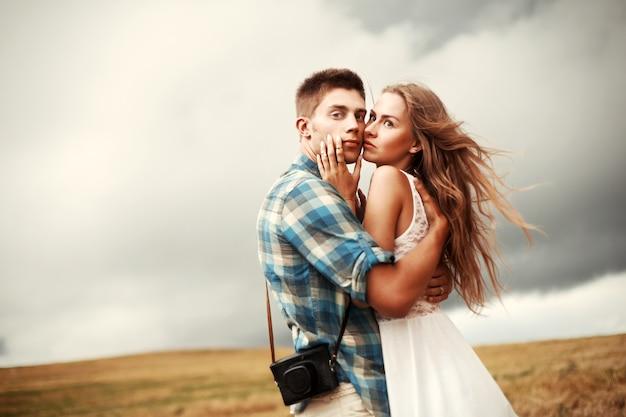 曇りの日に彼のガールフレンドを抱いガイ