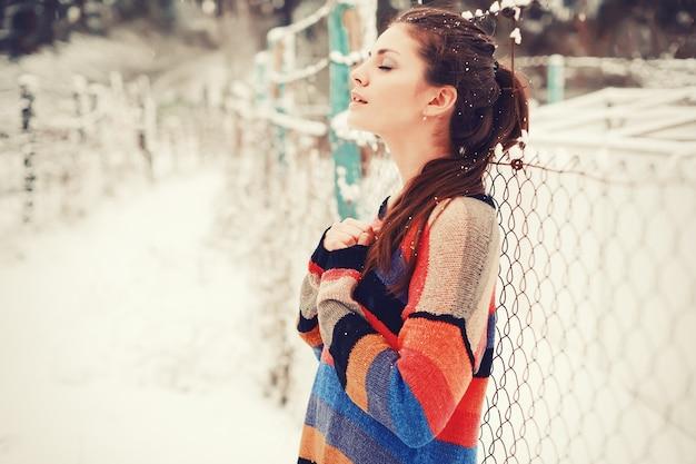 雪の中でリラックスした若い女性