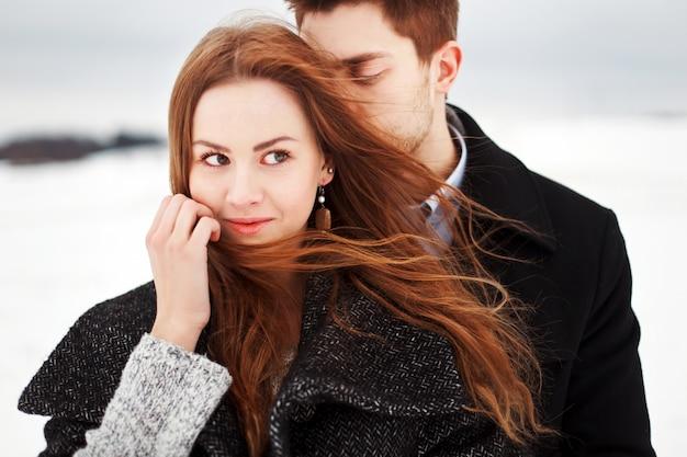 雪で覆われた分野で若いカップルのクローズアップ