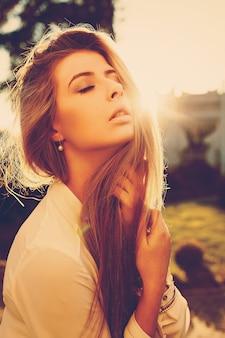 屋外で夕日を楽しんで長い髪の若い女性