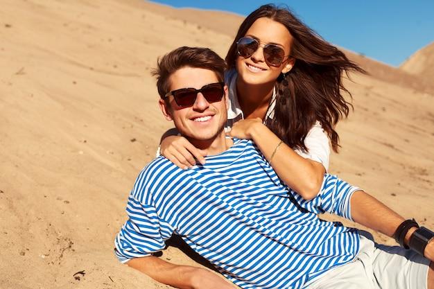 砂の上に横たわっているサングラスとロマンチックなカップル