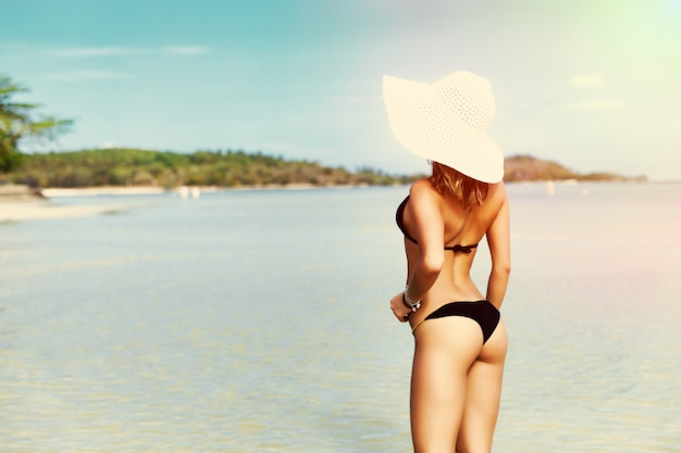 Вид сзади женщина в бикини, наслаждаясь видом