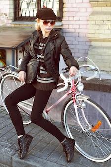 彼女の自転車に座っ黒いハンドバッグのエレガントな女性