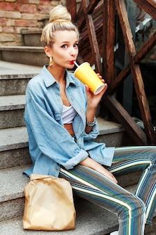 Молодая женщина, сидя на лестнице и питьевой соды