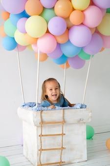 小さな女の子が風船かごの中に立ち笑います。誕生日、休日の装飾