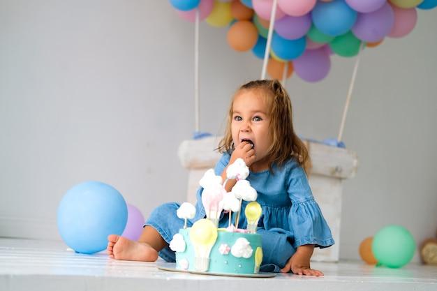 誕生日の女の子は誕生日ケーキを持って幸せです。背景には、色のついたボールでできた大きなおもちゃの風船があります。