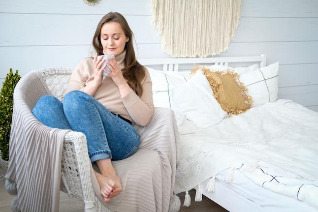Молодая женщина европейской внешности сидит на стуле и пьет чай с улыбкой на лице