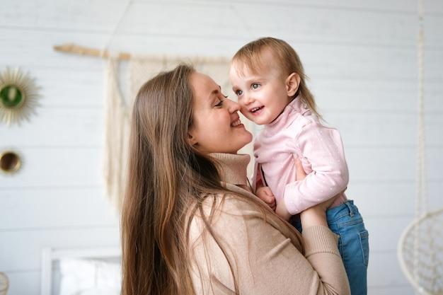 ママと娘は遊び、抱きしめて笑って幸せな家族