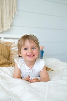 美しい少女はベッドに横になっていると笑っています