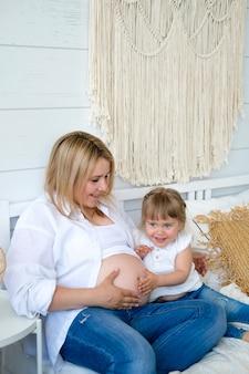 小さな女の子は寝室のベッドの上に座っている間彼女の母親の妊娠中の腹に耳を傾けます