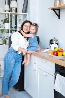 Счастливая мама и дочь на кухне. мама брюнетки в белой рубашке и джинсах