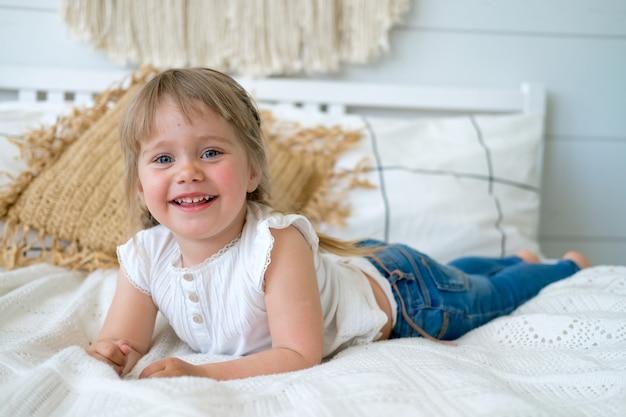 ひもを持つ美しい少女はベッドに横になって笑っています。