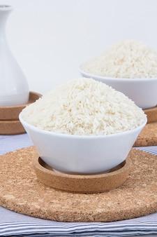 米、浅い被写界深度、米に焦点を当てた白いセラミックボウル。