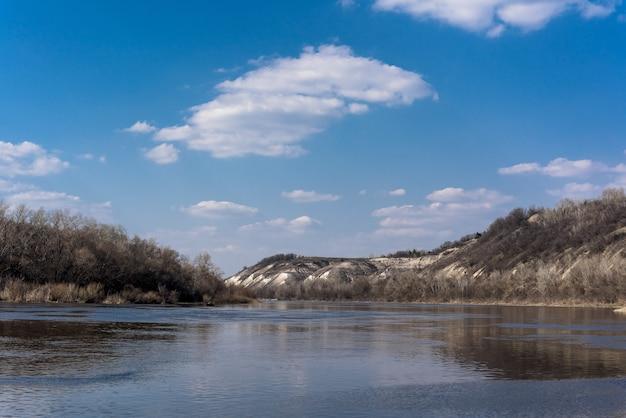 川のパノラマ。広いチャンネル、青い空。山岸