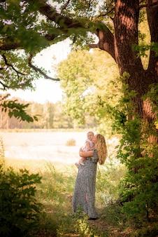 Мать и дитя в осеннем лесу играют