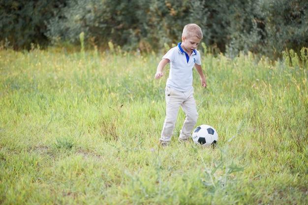 子供たちはフィールドでサッカーボールをプレイします。スポーツ服を着て