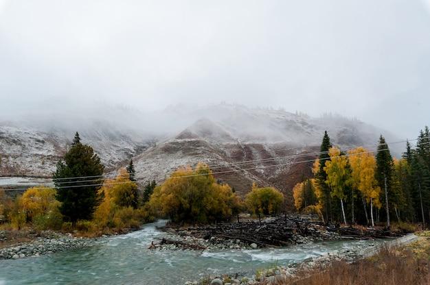 雪で覆われた山の背景に青緑色の川