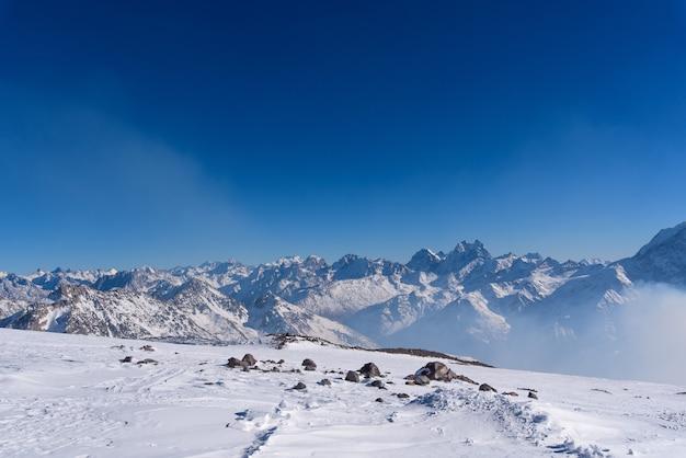 エルブルス地方のコーカサス山脈。部分的に雪で覆われています。冬の山の風景