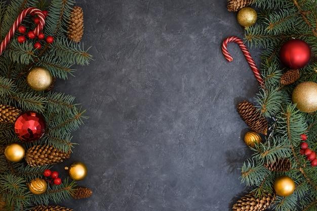モミの枝、クリスマスボール、キャンディー、松ぼっくりのクリスマス組成。両側の暗い背景。上からの眺め