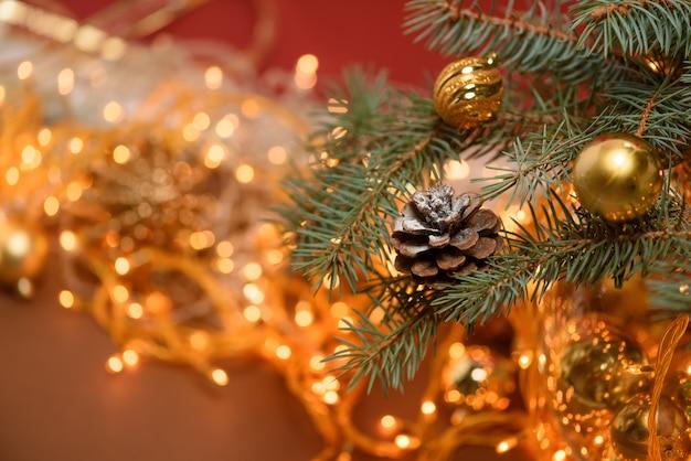 Рождественская еловая шишка на еловой ветке на фоне рождественской гирлянды