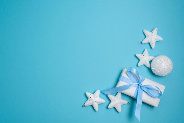 Рождественская композиция из белых шаров и подарок с голубой лентой на синем фоне.