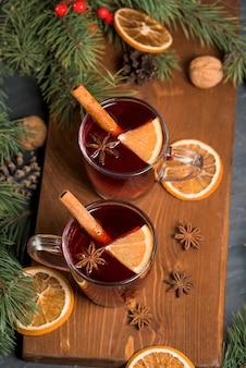 クリスマスの赤ワインは、香り豊かなスパイスと木製のテーブルに柑橘系の果物とホットワインクローズアップ。