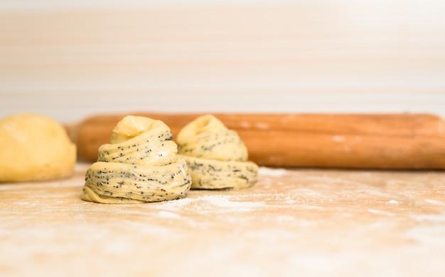 Сырые булочки перед запеканием в духовке. слоеное тесто, похожее на булочку с маком, свернутое в рулет.