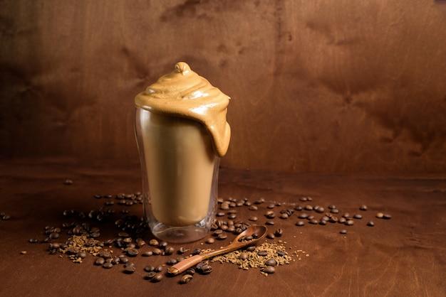 Холодный кофе дальгон в прозрачных очках на темном деревянном фоне