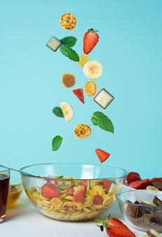 シリアル用ミニパンケーキボウル、新鮮なイチゴ、バナナ、チョコレート、ココナッツミント。青色の背景にあるプレートに小さなパンケーキの浮上