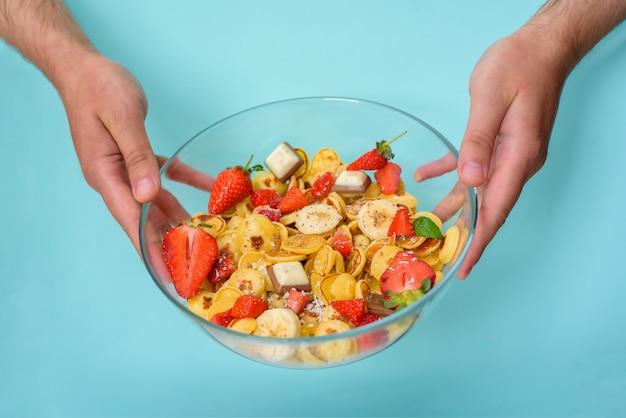 小さなパンケーキボウルシリアル、新鮮なイチゴ、バナナ、チョコレート、ココナッツの削りくず、青色の背景に受け皿に蜂蜜。ボウルを持っている手
