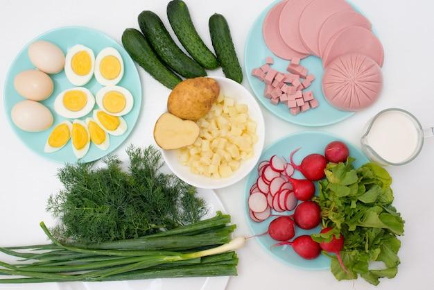 ロシアの冷たいオクロシカスープの材料、自家製オクロシカソーセージの材料、青菜、卵、きゅうり、ジャガイモ、大根。上からの眺め