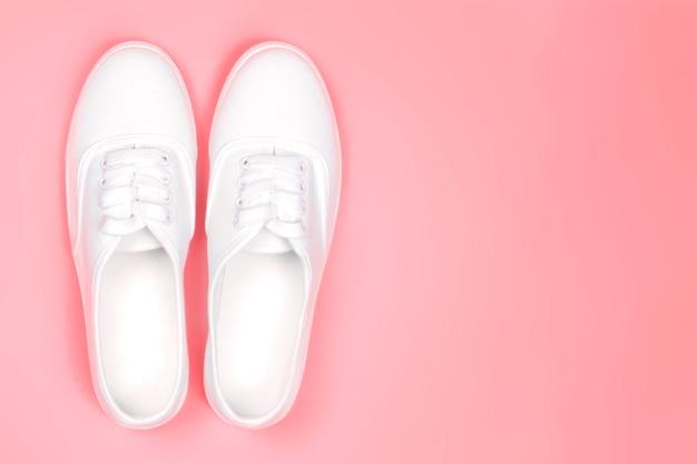 ピンクの背景のクローズアップに白いスニーカー、コピースペース靴のファッショントレンド。
