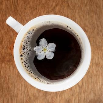 Чашка кофе на деревянной предпосылке, взгляд сверху. время весны