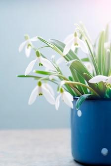 Весенние белые подснежники в старинной синей кружке. время весны