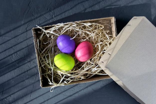 黒い壁のボックスに着色された卵、上面図の表示。イースターのコンセプトです。
