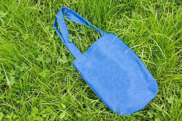 Джинсовая эко сумка на зеленой траве.
