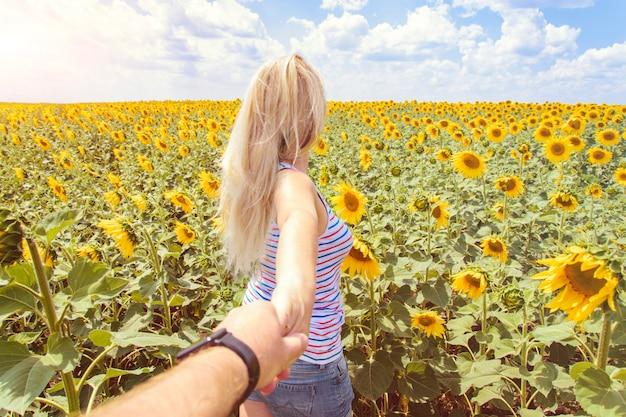 私に従ってください-若い女性が手で男を引っ張る-晴れた日にひまわり畑で手をつないで歩く-のんきな現代生活の概念