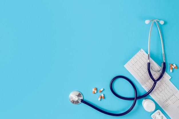 聴診器、心電図、コピースペース、トップビューで青色の背景に薬。心臓病、心臓病の概念。