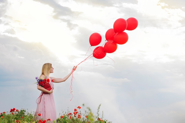 Девушка с красными воздушными шарами в маковом поле, скопируйте космос. романтическая любовь фото
