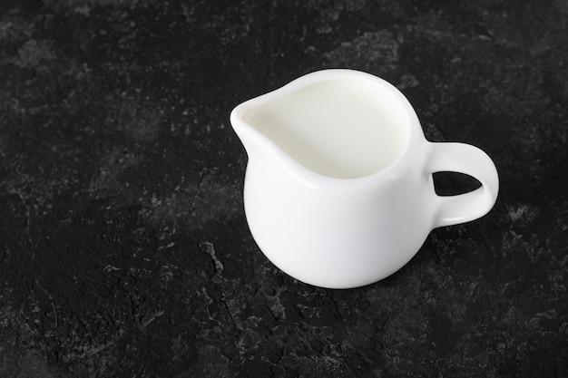 コピースペースと黒の背景の水差しミルク