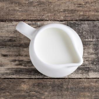 素朴なスタイルの木製のテーブルの上のミルク水差しのオーガニックミルク。