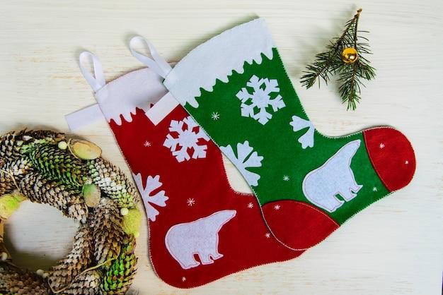 白い背景の上の装飾とクリスマスの赤と緑の靴下