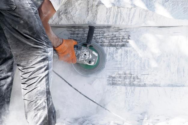 労働者は白い石の上で粉砕機として働いています。