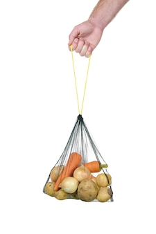 白の手で野菜と食料品のエコバッグ