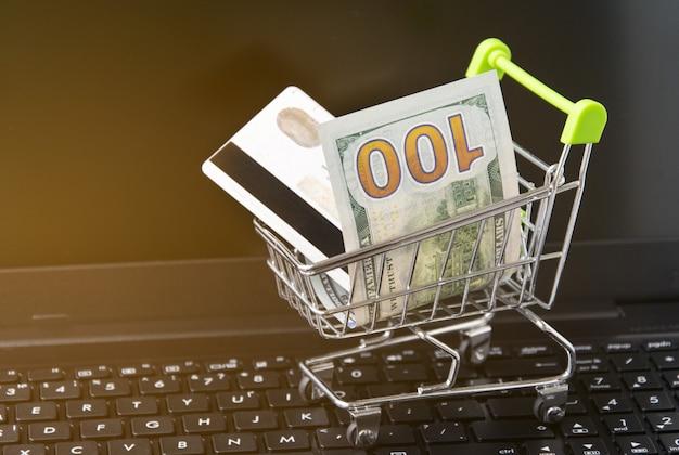 お金とラップトップ上のカードを備えた小さなショッピングトロリー。オンラインショッピングの概念
