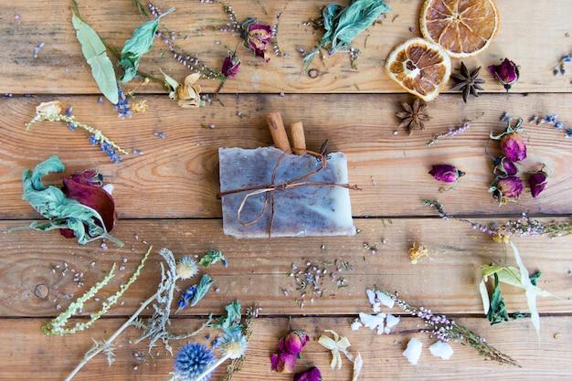 木製の背景の上面にシナモンと自然化粧品の石鹸。