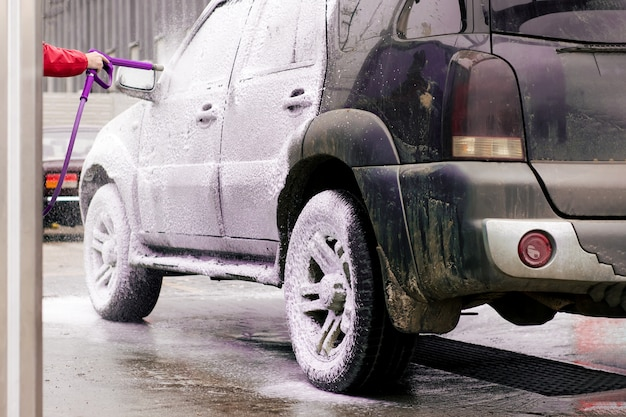 汚れた車が流し台のスプレーから活発な泡で吹き出す