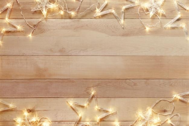 Деревянная предпосылка рождества с яркой гирляндой. копировать пространство