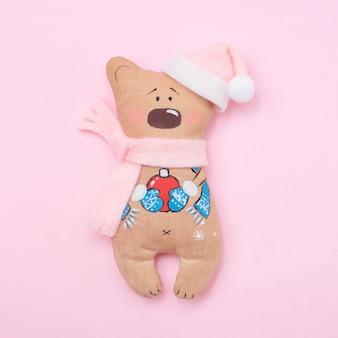 ピンクの背景に手作りのかわいいテディベアサンタ