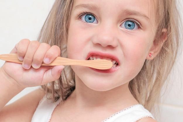美しい青い目を持つ少女は、竹の歯ブラシで歯を磨きます。クローズアップの肖像画。